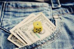 Un dólar en dril de algodón del bolsillo y un dado Imagen de archivo libre de regalías