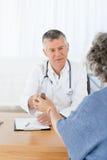 Un docteur aîné avec son patient Photographie stock libre de droits