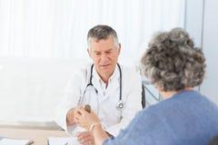 Un docteur aîné avec son patient Image stock