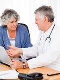 Un docteur aîné avec son patient Images stock
