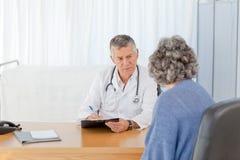 Un docteur aîné parlant avec son patient Photo stock