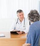 Un docteur aîné parlant avec son patient Image libre de droits