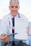 Un docteur affichant une feuille blanc de prescription Photographie stock libre de droits