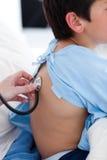 Un docteur contrôlant la cadence respiratoire d'un enfant Photos stock