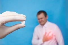 Un docteur dans un gant médical tenant une pilule pour les maladies du système cardio-vasculaire, un patient masculin tenant son  photo stock