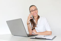 Un docteur With de jeune femme un ordinateur portable dans son bureau parlant au téléphone images stock