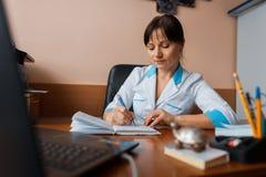 Un docteur féminin dans l'uniforme blanc s'assied à une table en bois dans son bureau et écrit quelque chose dans un carnet Jours photo stock