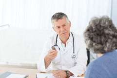 Un docteur aîné parlant avec son patient Image stock