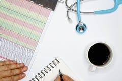un docteur prenant la note sur le patient& x27 ; état de s photographie stock