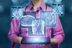 Un docteur tenant un comprimé avec des résultats numériques des images d'organes internes photo stock