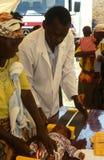 Un docteur tendant à une chéri, Rwanda Photos stock
