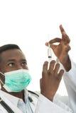 Un doctor afroamericano que sostiene una jeringuilla imagen de archivo