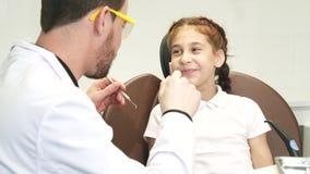 Un doctor bueno examina los dientes de una niña metrajes