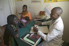 Un doctor consulta con la madre y los niños sobre HIV/AIDS en Pepo La Tumaini Jangwani, programa de rehabilitación de la comunida Imagen de archivo