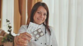 Un doctor de la chica joven demuestra en las manos de un paquete de píldoras almacen de video