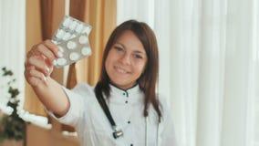 Un doctor de la chica joven demuestra en las manos de un paquete de píldoras Imágenes de archivo libres de regalías