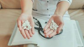 Un doctor de la chica joven vertió las píldoras blancas de mano a mano Fotos de archivo libres de regalías