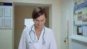 Un doctor de la mujer camina abajo del pasillo de la policlínico Cámara lenta Primer almacen de metraje de vídeo
