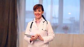 Un doctor de la mujer en el hospital con la tableta almacen de video