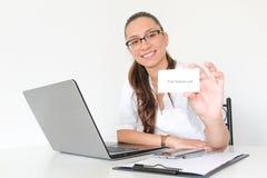 Un doctor de la mujer joven con un ordenador portátil en su oficina sostiene una tarjeta de visita Foto de archivo libre de regalías