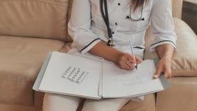 Un doctor de la mujer joven escribe medicaciones de la prescripción y consejo del tratamiento almacen de video