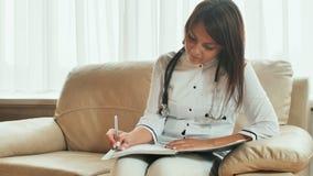 Un doctor de la mujer joven escribe medicaciones de la prescripción y consejo del tratamiento imagenes de archivo