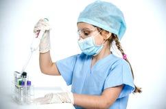 Un doctor de la niña en un casquillo, una máscara, gafas del plástico protector y guantes médicos sostiene un dispensador en sus  Fotografía de archivo