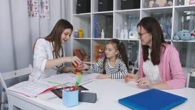 Un doctor de los niños La madre y la hija comunican con los doctores en la oficina en el hospital de niños metrajes