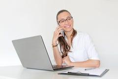 Un doctor With de mujer joven un ordenador portátil en su oficina que habla en el teléfono Imagenes de archivo