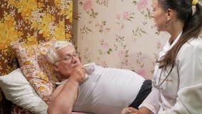 Un doctor de sexo femenino da una píldora de una enfermedad casera El hombre es agua potable, mintiendo en el sofá almacen de metraje de vídeo