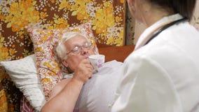 Un doctor de sexo femenino da una píldora de una enfermedad casera El hombre es agua potable, mintiendo en el sofá metrajes