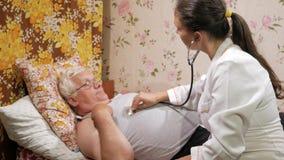 Un doctor de sexo femenino escucha un paciente con un phonendoscope en casa El hombre está mintiendo en el sofá metrajes