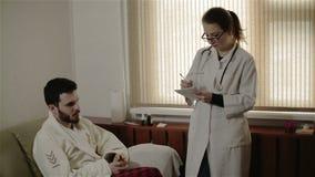 Un doctor de sexo femenino joven que escribe una prescripción para un paciente almacen de metraje de vídeo