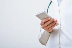 Un doctor de sexo femenino que manda un SMS en smartphone Imagenes de archivo