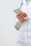 Un doctor de sexo femenino que manda un SMS en smartphone Foto de archivo libre de regalías