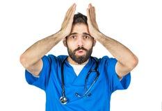 Un doctor de sexo masculino es trastornado o preocupante Aislado en la parte posterior blanca del estudio imágenes de archivo libres de regalías