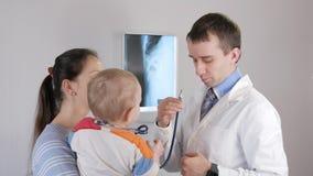 Un doctor de sexo masculino joven da un juego a un niño con un estetoscopio El muchacho está en sus brazos del ` s de la madre almacen de video