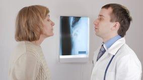 Un doctor de sexo masculino joven examina la garganta de una mujer envejecida El hombre dice la diagnosis y prescribe el tratamie metrajes