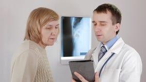 Un doctor de sexo masculino joven muestra los resultados de pruebas en una tableta El paciente es una mujer envejecida almacen de video