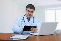 Un doctor de sexo masculino mira la tableta Imágenes de archivo libres de regalías