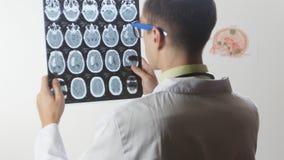 Un doctor del neurocirujano mira una foto de resonancia magnética de la proyección de imagen MRI del cerebro almacen de video
