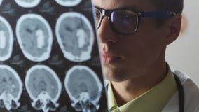 Un doctor del neurocirujano mira una foto de resonancia magnética de la proyección de imagen MRI del cerebro El doctor diagnostic almacen de metraje de vídeo