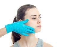 Un doctor en un guante azul toca la mejilla de una chica joven sin el maquillaje que mira hacia el primer foto de archivo libre de regalías