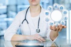 Un doctor es que sienta y que lleva a cabo un círculo de iconos con símbolos médicos foto de archivo libre de regalías