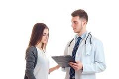 Un doctor joven en una bata y con la tableta en sus manos explica algo muchacha Fotografía de archivo libre de regalías