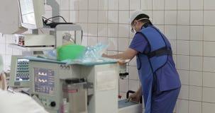Un doctor joven en uniforme mueve el equipo médico de la radiografía en la sala de operaciones almacen de video