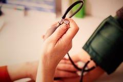 Un doctor mide la presión sobre un hombre imagenes de archivo