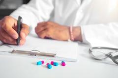 Un doctor prescribe la medicación las píldoras de la prescripción son prescritas por un doctor fotos de archivo libres de regalías
