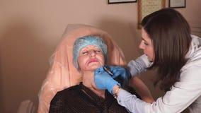 Un doctor privado hace terapia botulinum a una mujer en el área de juntas orales almacen de video