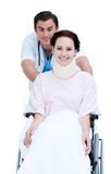 Un doctor que lleva a un paciente en un sillón de ruedas Imagen de archivo libre de regalías